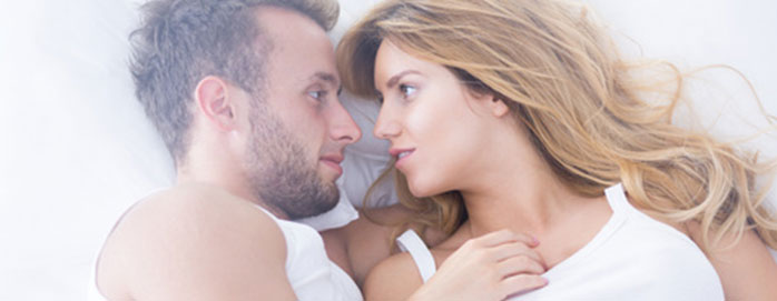 Erectile dysfunction treatment concept - couple lying on bed.