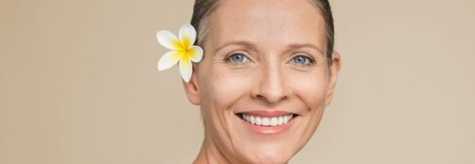 Smiling Woman With a Flower in Her Ear