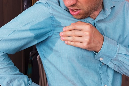 man looking in horror at a sweat stained shirt - excessive sweating