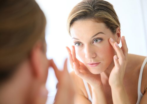 Woman in the mirror dealing with winter skin problems.