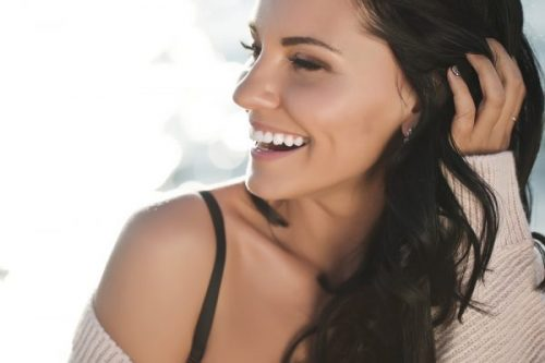 Smiling woman with nice shape of nose from non-surgical nose job.