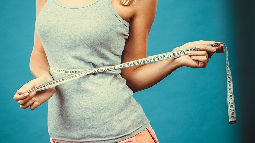 Woman with measuring tape on waist after non-surgical weight loss treatment.