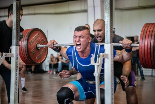 Man doing power lifting assisted by trainer.