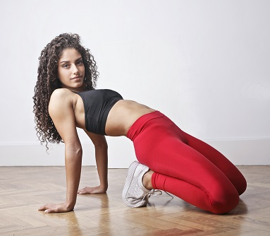 woman in black tank top and red leggings exercising.