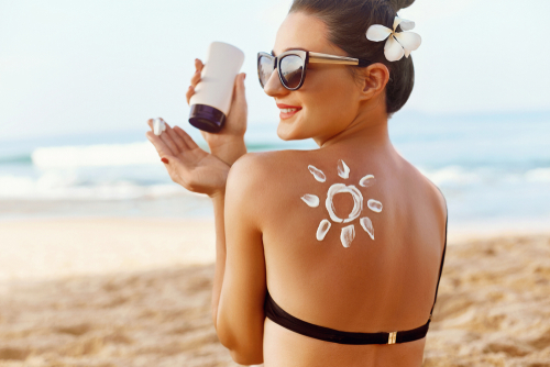 woman on a beach applying sunscreen to protect her skin from UV