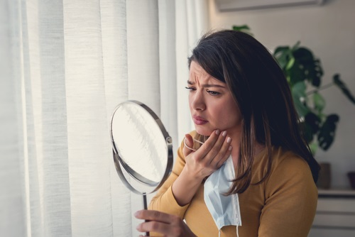 Woman looking herself in the mirror at home. She is concerned about acne, maskne