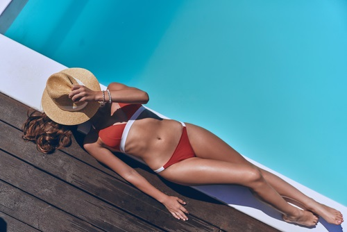 young woman tanning herself by a pool